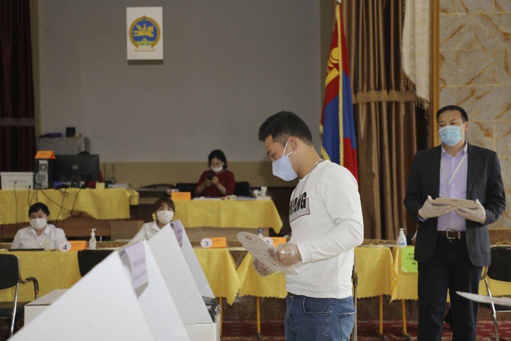 A voter stands in front of a ballot machine as election observers watch in the background at a polling station in Ulaanbaatar, Mongolia on Wednesday, ...