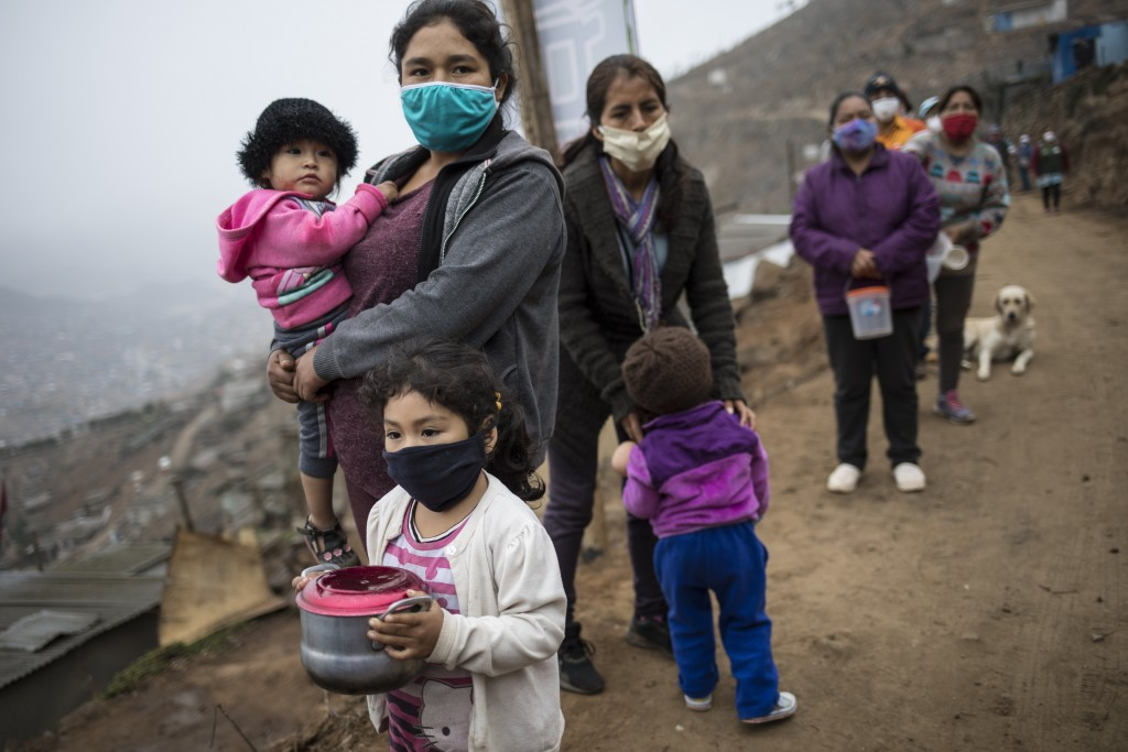 FILE - In this June 17, 2020, file photo, people wearing masks to curb the spread of the new coronavirus wait in a line for a free meal at the Villa M...