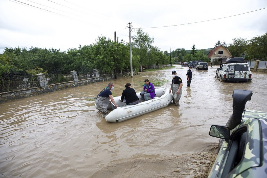 Ukraine's Emergency Situation workers evacuate residents of the flooded village of Lanchyn in the Ivano-Frankivsk region, western Ukraine, Wednesday, ...
