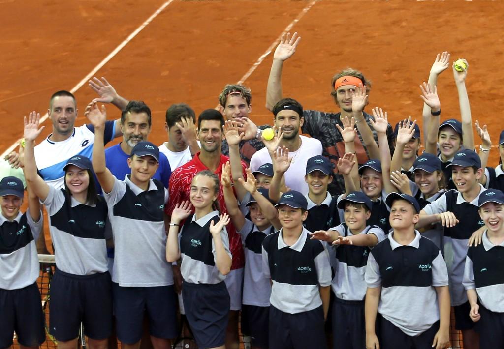 In this photo taken on Friday, June 12, 2020, Serbia's Novak Djokovic, centre, poses with volunteers and players during the Adria Tour charity tournam...