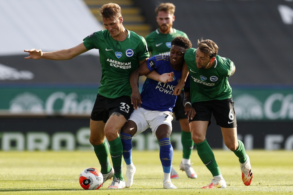 Leicester's Demarai Gray, center, fights for the ball with Brighton's Dale Stephens, left, and Dan Burnduring during the English Premier League soccer...