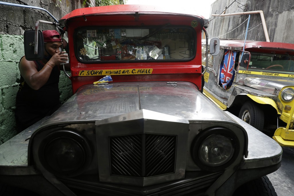 A jeepney driver drinks coffee beside his vehicle at the Tandang Sora terminal which have been home for them since a lockdown started three months ago...
