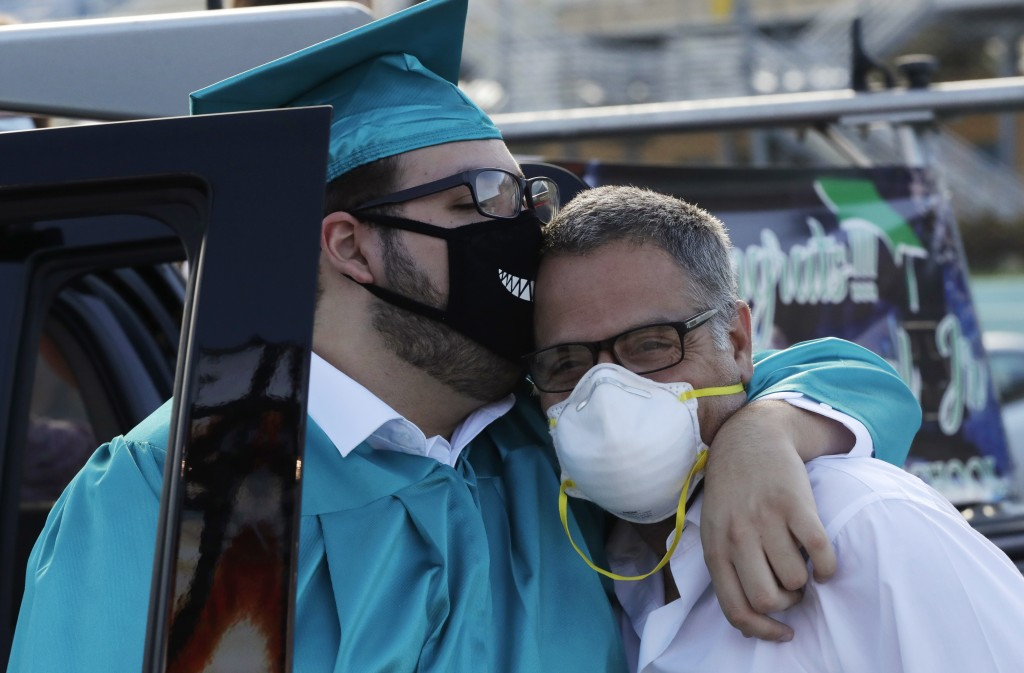 Ariel Amengual Jr., left, hugs his father, Ariel Amengual, during a graduation ceremony for the senior class of Chambers High School at Homestead-Miam...