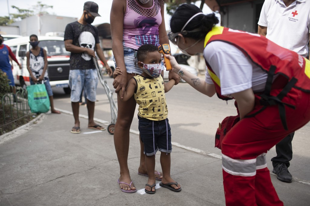 A member of the Red Cross checks the temperature of a child at the CEASA, Rio de Janeiro's main wholesale market, amid the new coronavirus pandemic in...
