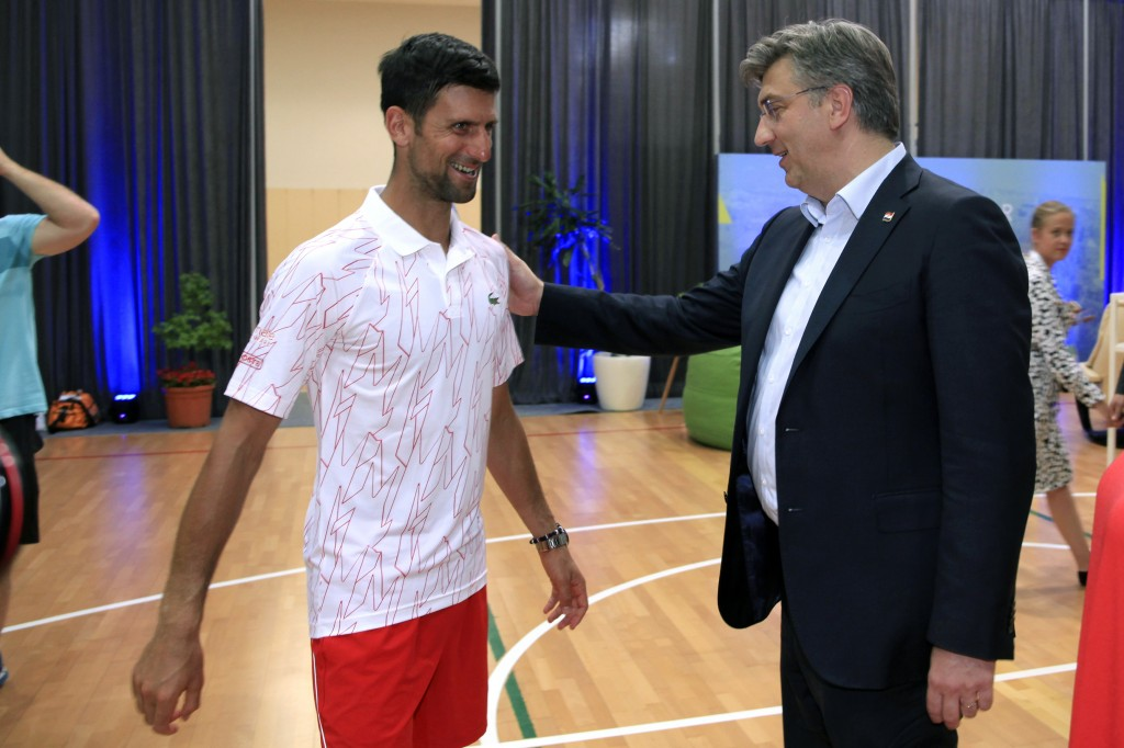 In this photo taken on Saturday June 20, 2020 and provided by the Croatian Tennis Association, Croatian Prime Minister Andrej Plenkovic, right, greets...