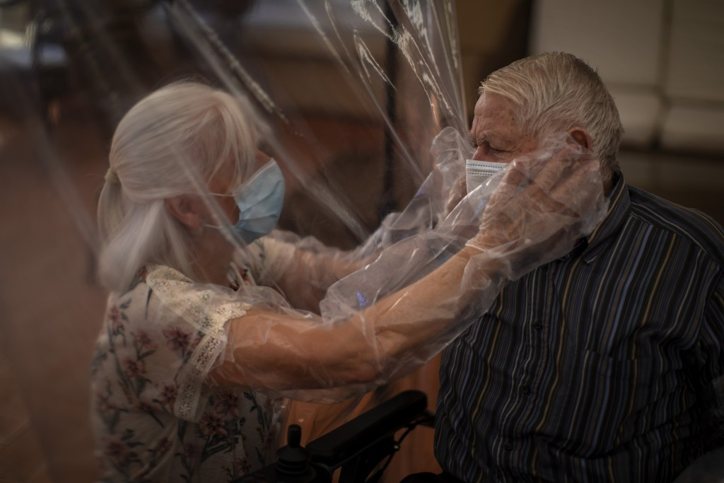 In this Monday, June 22, 2020 photo, Dolores Reyes Fernández, 61, touches the face of her father José Reyes Lozano, 87, for the first time in nearly f...