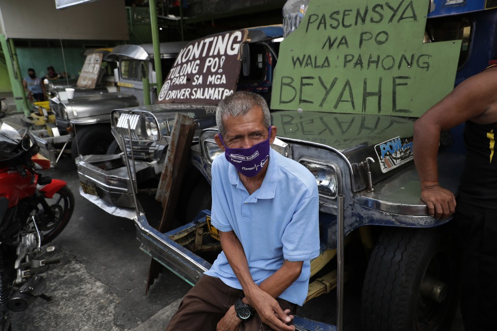 "Driver Arthur Vinluan, 62, sits on a passenger jeepney beside a sign that says ""sorry we're not yet in operation"" at the Tandang Sora terminal which h..."