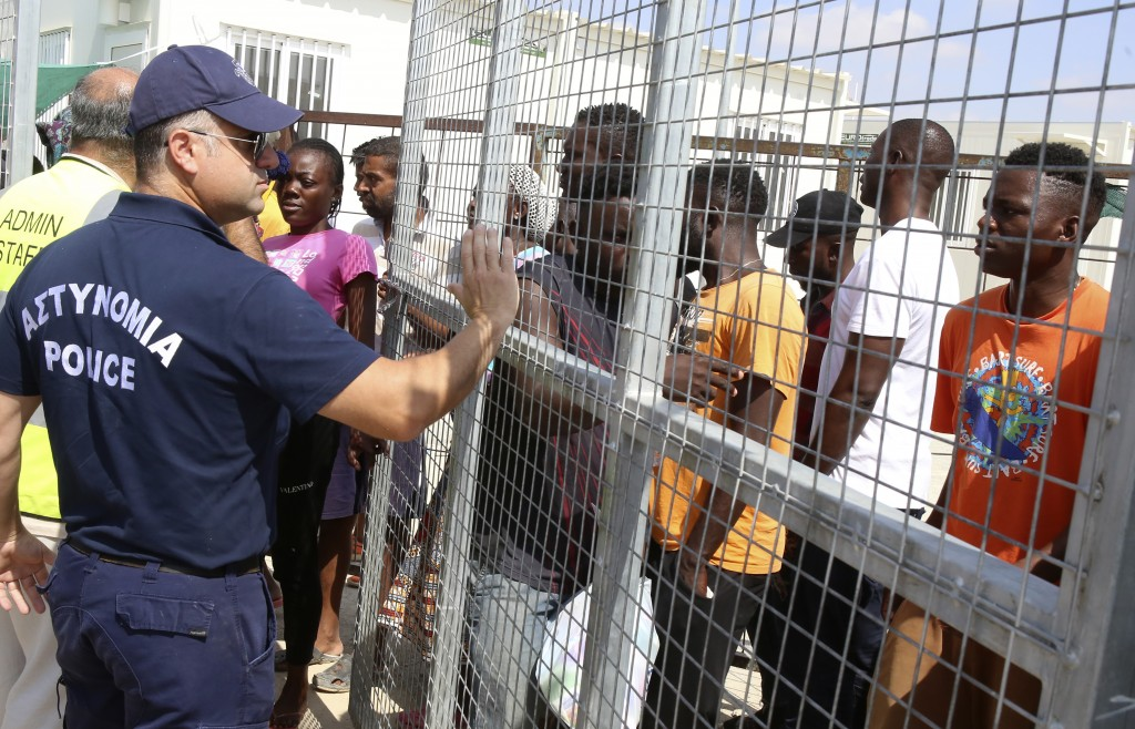A police officer stands guard as migrants stand inside a refugee camp in Kokkinotrimithia outside of Nicosia, Cyprus, on Tuesday, June 23, 2020. Cypru...
