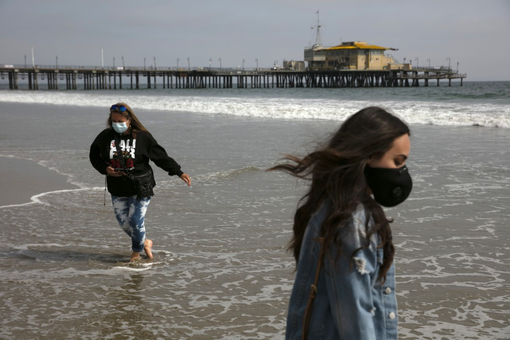 Malia Pena, foreground, and her mother, Lisa Torriente, wear masks as they visit the beach Tuesday, June 23, 2020, in Santa Monica, Calif. The state D...