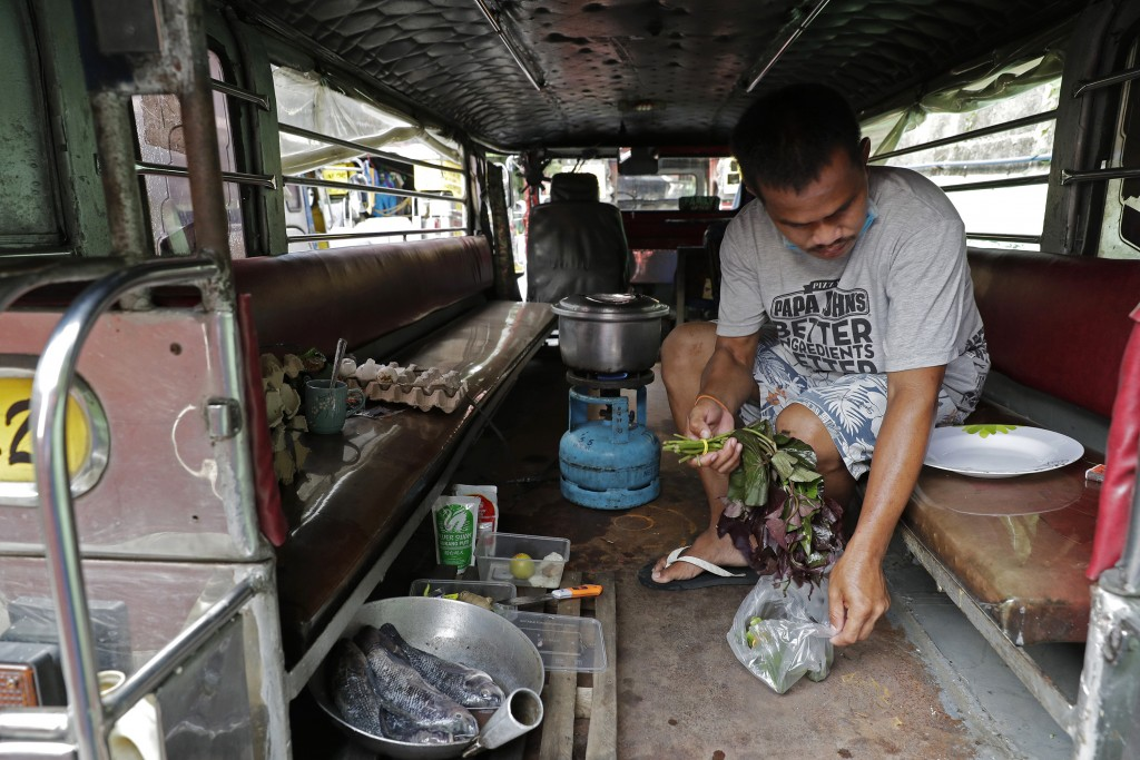Driver Michael Navarra cooks fish and vegetables on their portable stove inside a jeepney at the Tandang Sora terminal which have been home for them s...