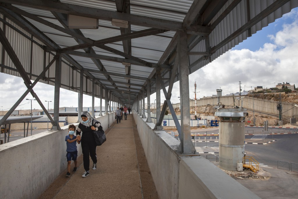 In this Friday, June 19, 2020 photo, Palestinians cross a bridge at Qalandia checkpoint between the West Bank city of Ramallah and Jerusalem, Friday, ...