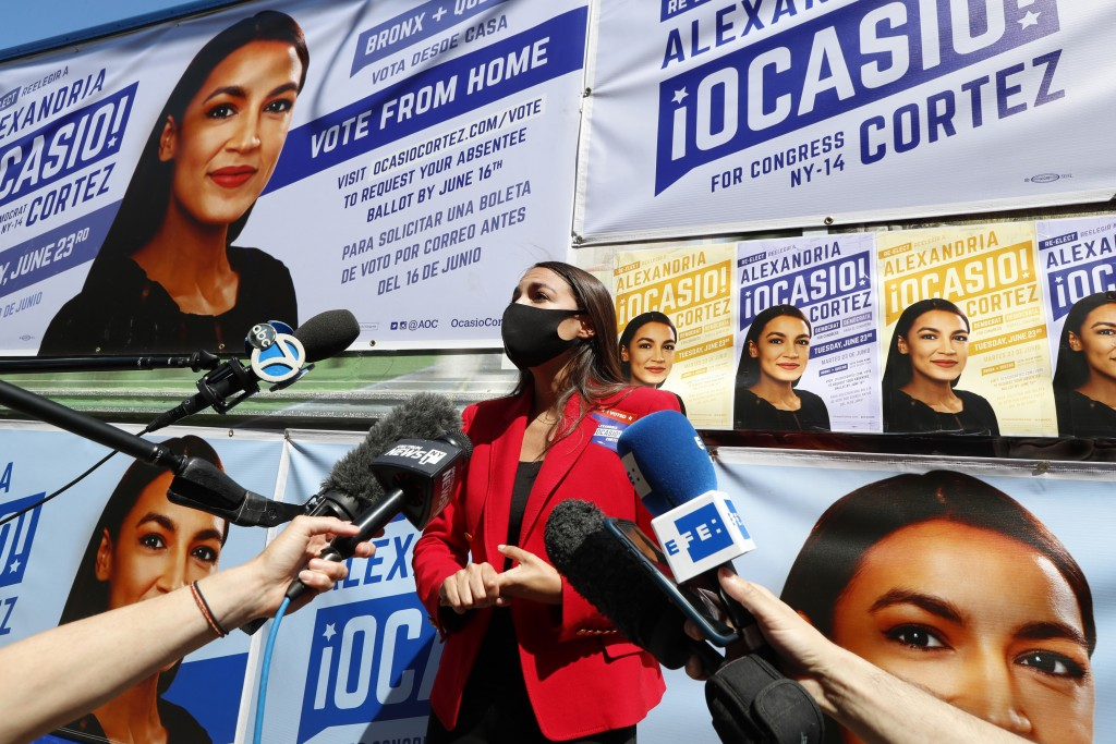 U.S. Rep. Alexandria Ocasio-Cortez, D, New York, center, speaks to members of the media while standing beside a truck plastered with campaign posters ...