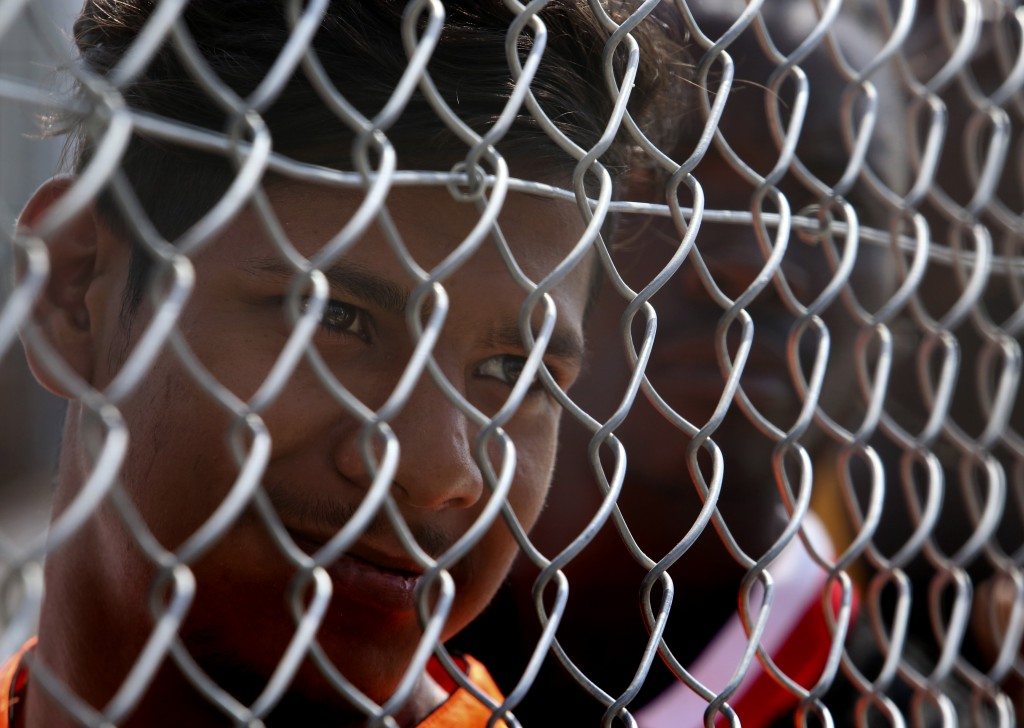 A migrant stands behind a fence inside a refugee camp in Kokkinotrimithia outside of capital Nicosia, Cyprus, on Tuesday, June 23, 2020. Cyprus' inter...