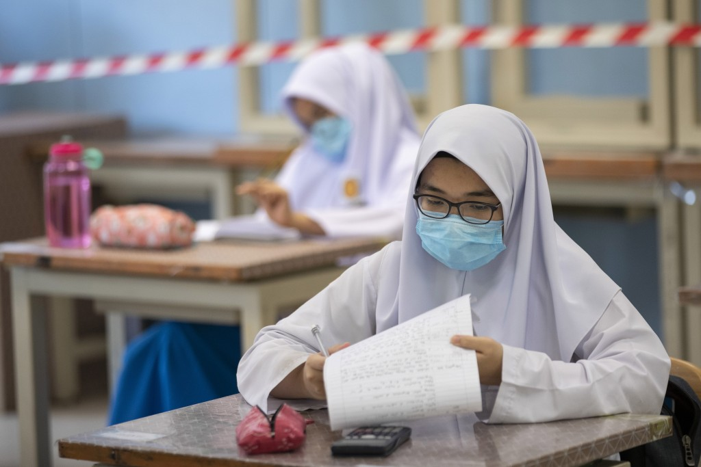 Students wearing face masks and maintaining social distancing at a classroom during the first day of school reopening at a high school in Putrajaya, M...