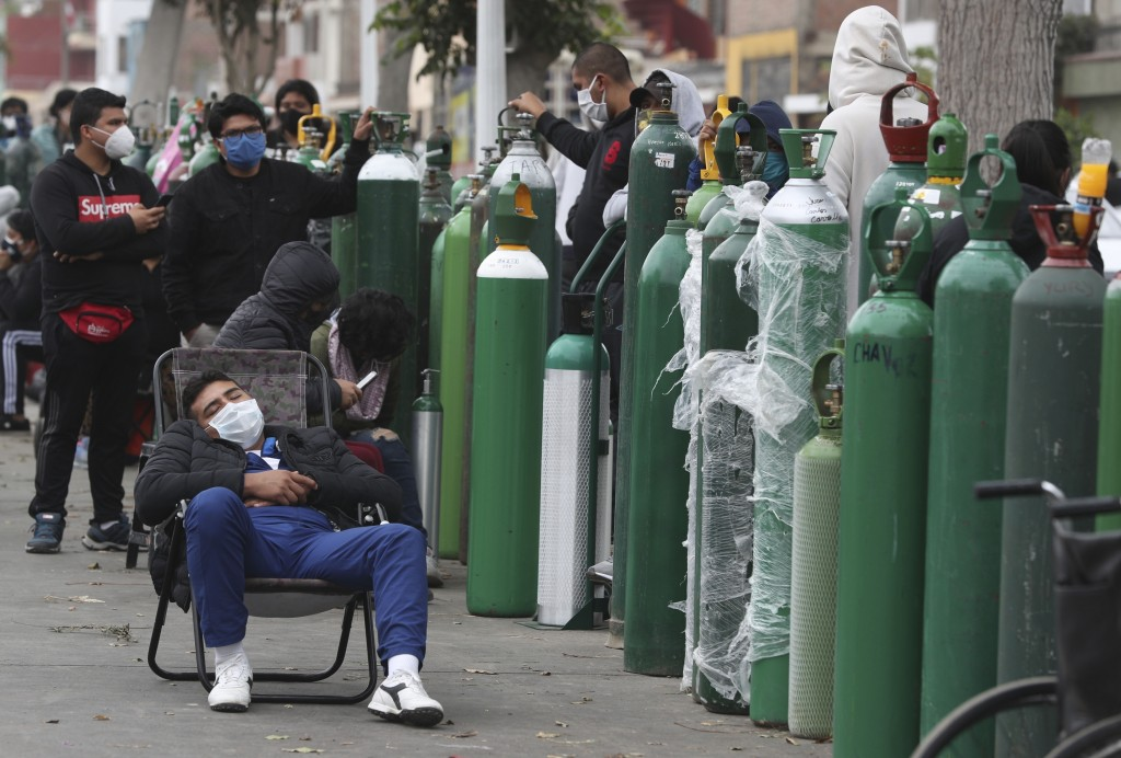 FILE - In this Monday, June 8, 2020 file photo, people wearing masks amid the COVID-19 coronavirus pandemic wait for hours, some for 10 hours, to refi...