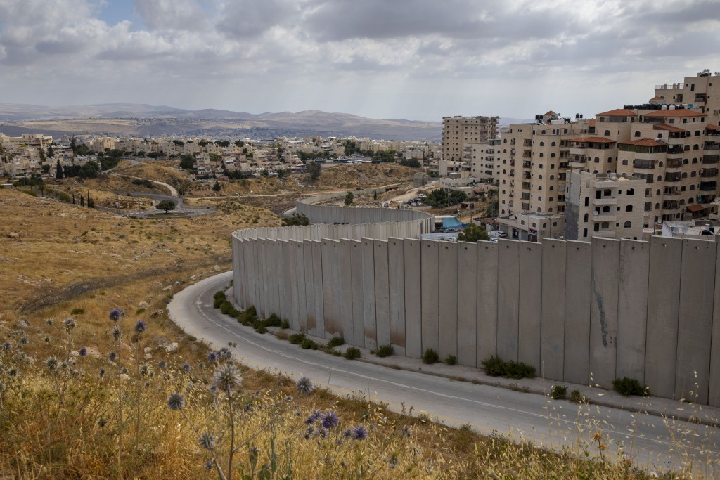 In this Friday, June 19, 2020 photo, A view of Shuafat refugee camp is seen behind section of Israel's separation barrier in Jerusalem, Friday, June 1...