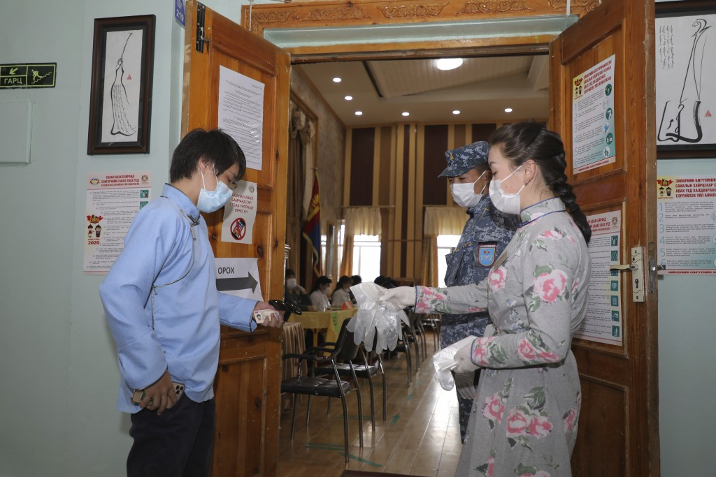 A resident is given plastic gloves as he arrives to vote at a polling station in Ulaanbaatar, Mongolia on Wednesday, June 24, 2020. Mongolians were vo...