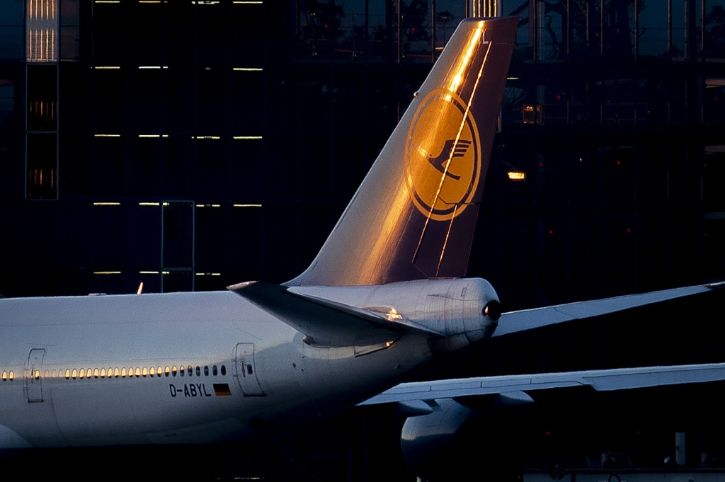 The setting sun illuminates the tail fin of a Lufthansa aircraft at the airport in Frankfurt, Germany, Tuesday, June 23, 2020. The German airline Luft...