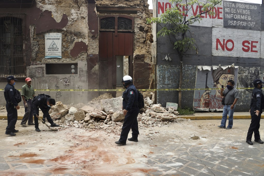A policeman removes rubble from a building damaged by an earthquake in Oaxaca, Mexico, Tuesday, June 23, 2020. The earthquake was centered near the re...