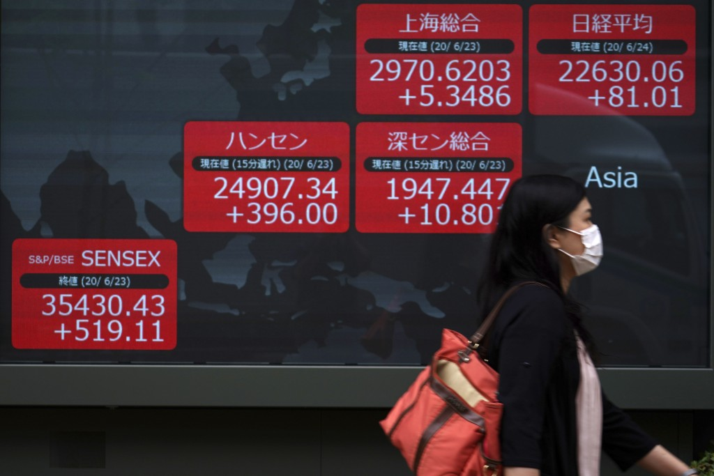 A woman walks past an electronic stock board showing Japan's Nikkei 225 and other Asian indexes at a securities firm in Tokyo Wednesday, June 24, 2020...