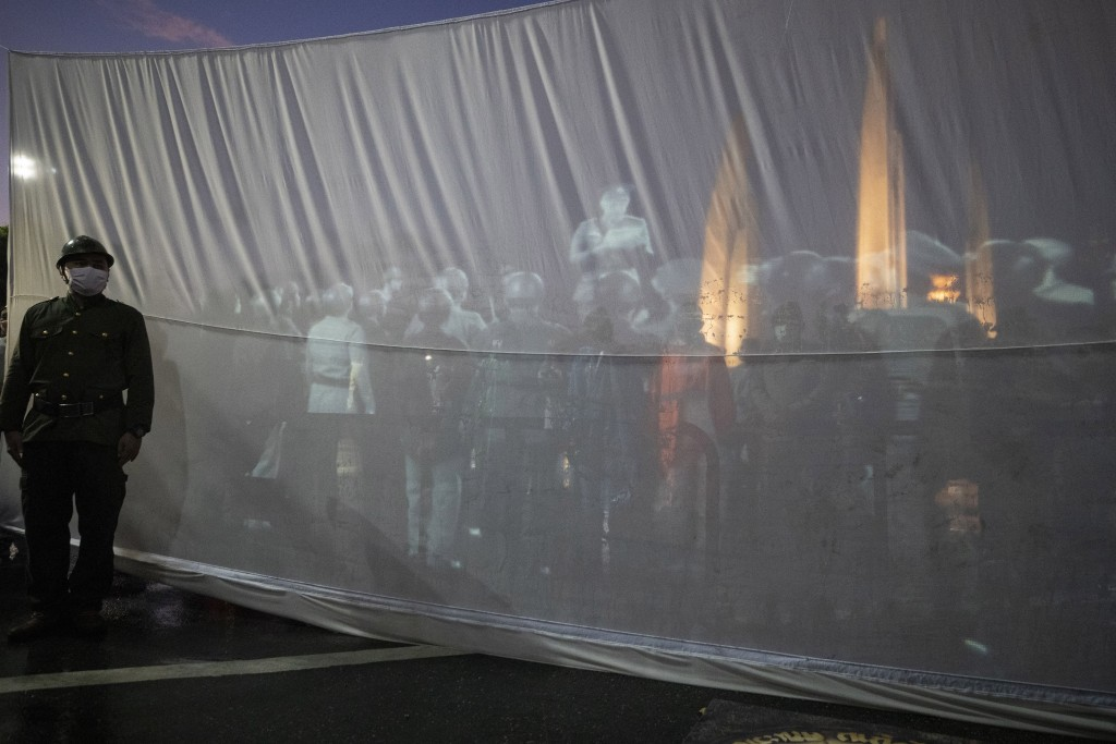 An anti-government activist in a soldier costume stands in front of video projection showing a re-enactment of the proclamation that ended absolute mo...