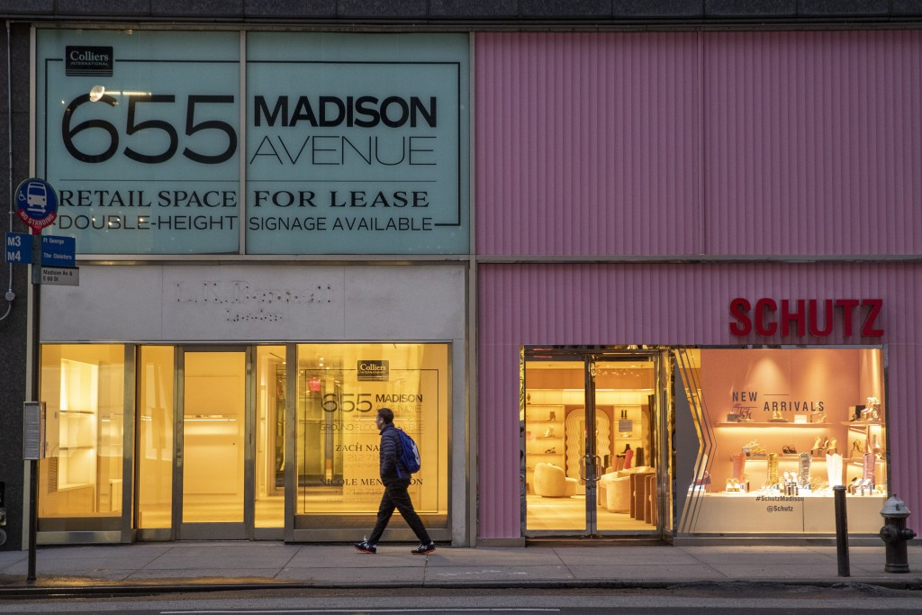 FILE- In this Thursday, March 19, 2020, file photo, a pedestrian walks past a storefront for rent on Madison Avenue, in New York. The coronavirus has ...