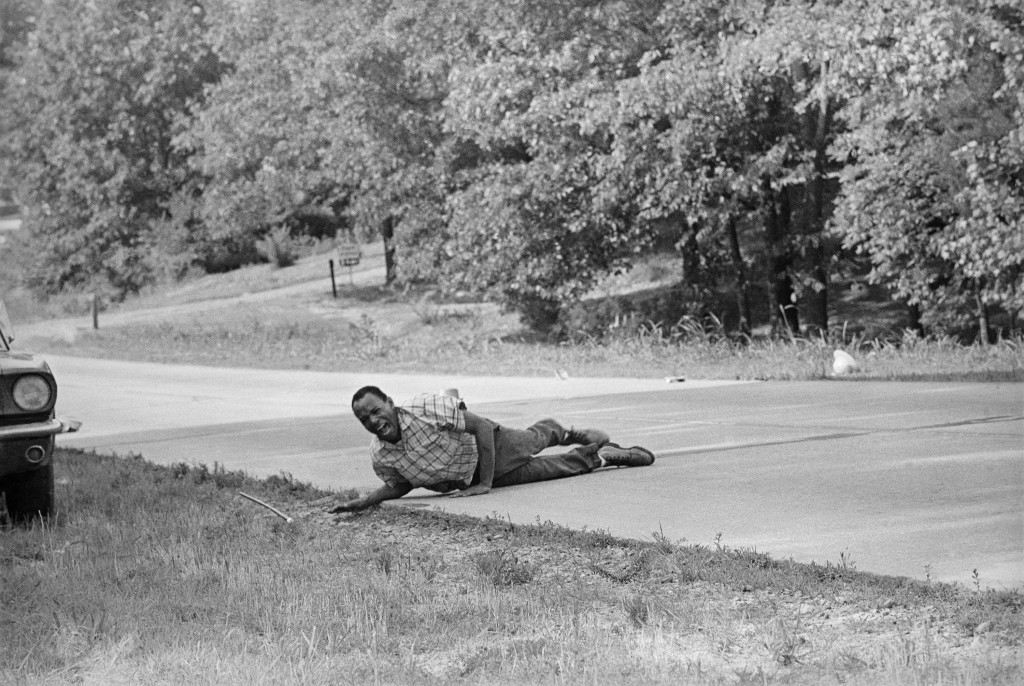 This June 6, 1966 file photo, shows civil rights activist James Meredith grimacing in pain as he pulls himself across Highway 51 after being shot in H...