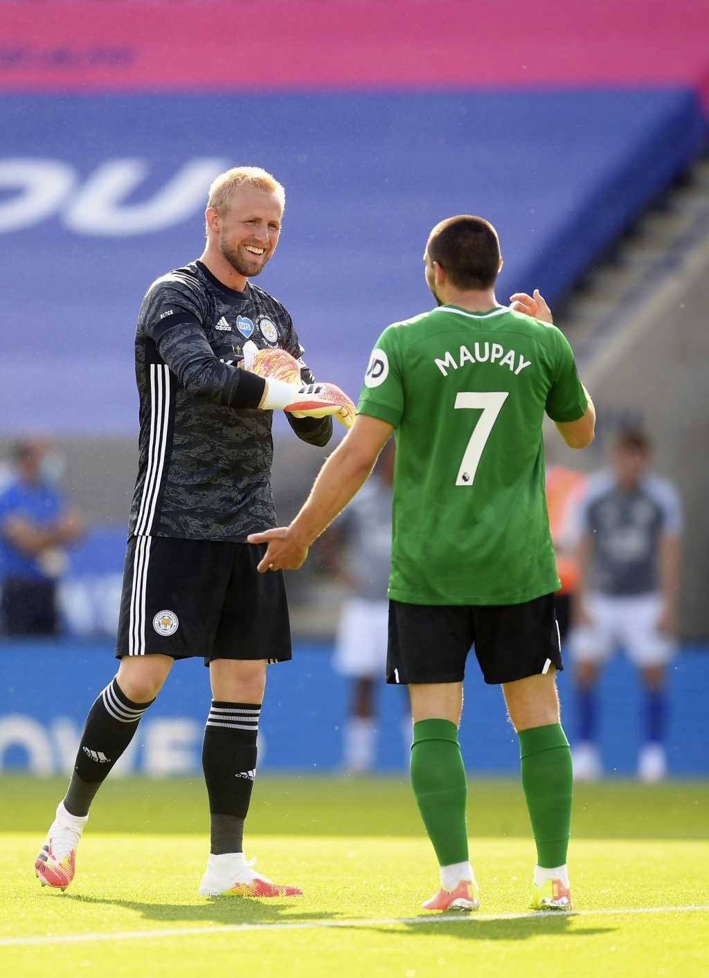 Leicester's goalkeeper Kasper Schmeichel, left, speaks with Brighton's Neal Maupay during the English Premier League soccer match between Leicester Ci...