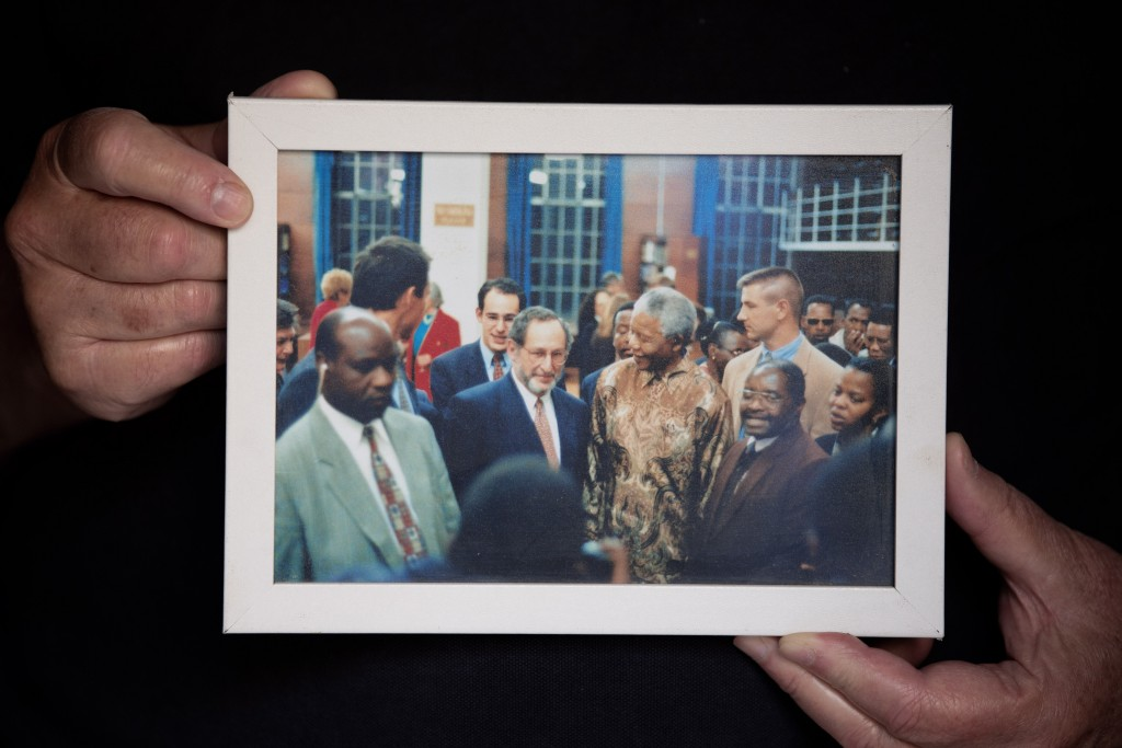 In this Friday, June 19, 2020 photo, Journalist and author Benjamin Pogrund holds a photo showing him, center, next to Nelson Mandela, at his house in...