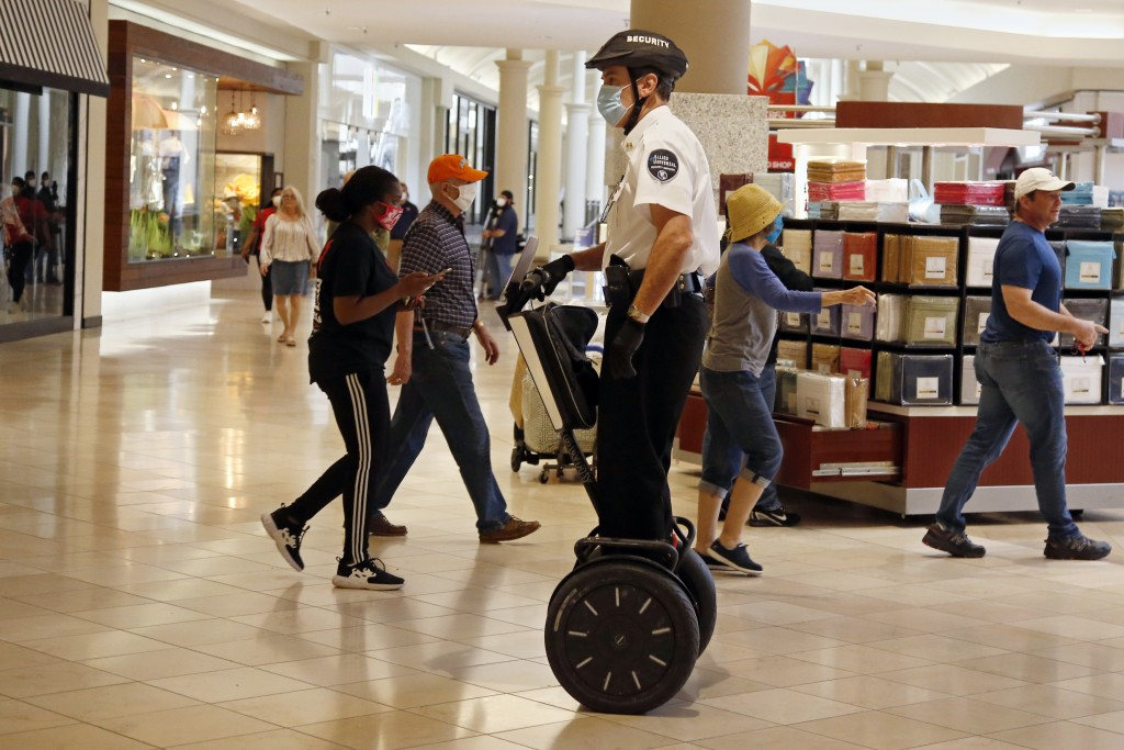 FILE - In this May 1, 2020 file photo, a security guard wearing a mask and riding a Segway patrols inside Penn Square Mall as the mall reopens in Okla...