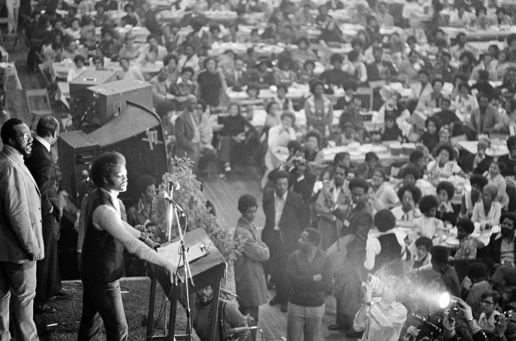 This March 26, 1972 file photo shows Rev. Jesse Jackson, left, speaking at a meeting held by Operation PUSH, a civil rights and economic organization,...