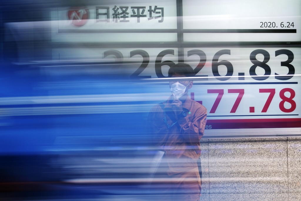 A man stands near an electronic stock board showing Japan's Nikkei 225 index as a vehicle passes by at a securities firm in Tokyo Wednesday, June 24, ...