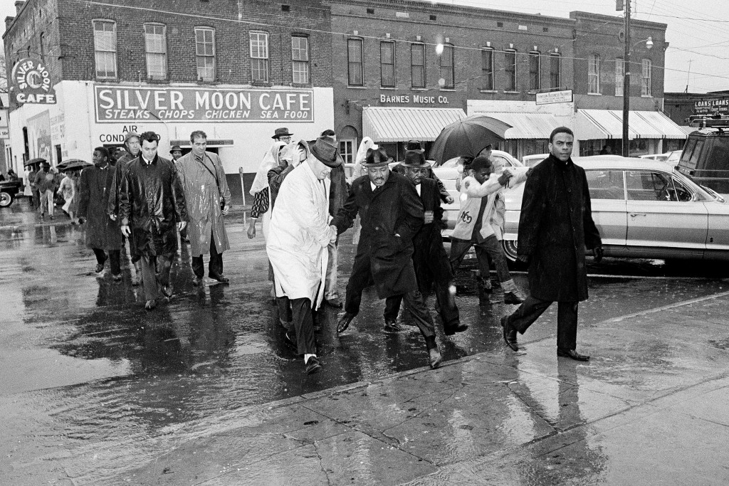 FILE - In this March 1, 1965 file photo Dr. Martin Luther King Jr. hops over a puddle as it rains in Selma, Ala. King led hundreds of African American...