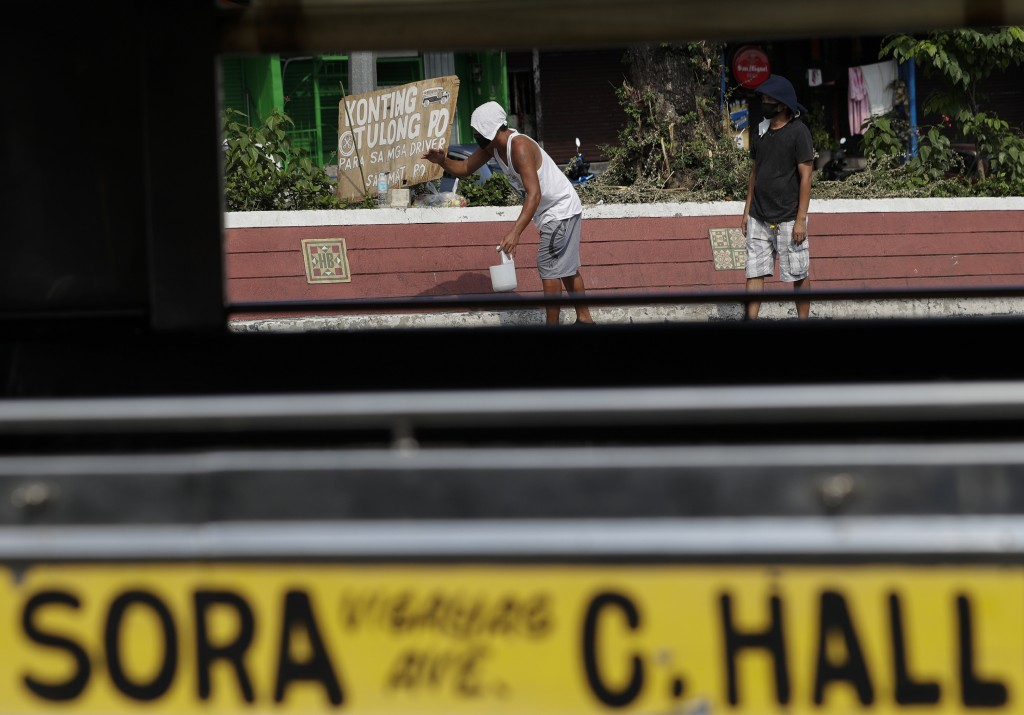 "Jeepney drivers beg for money beside a sign that says ""a little help please for the drivers, thank you"" in front of the Tandang Sora terminal which ha..."