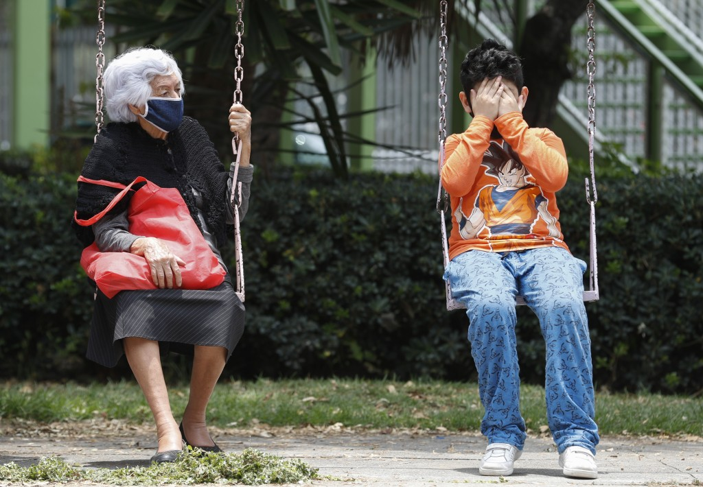 A woman and boy sit on a set of swings as they wait for the all-clear to return to their apartment, after an earthquake in Mexico City, Tuesday, June ...