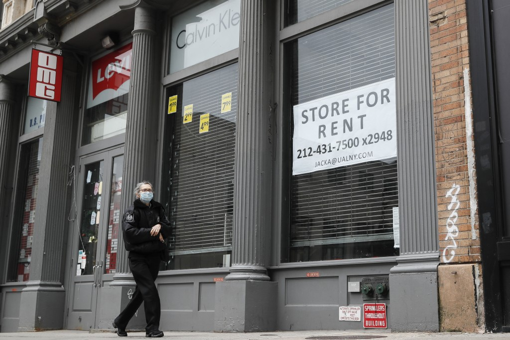 In this April 27, 2020 photo, a pedestrian passes a storefront available for rent on Broadway south of Canal Street  in the Manhattan borough of New Y...