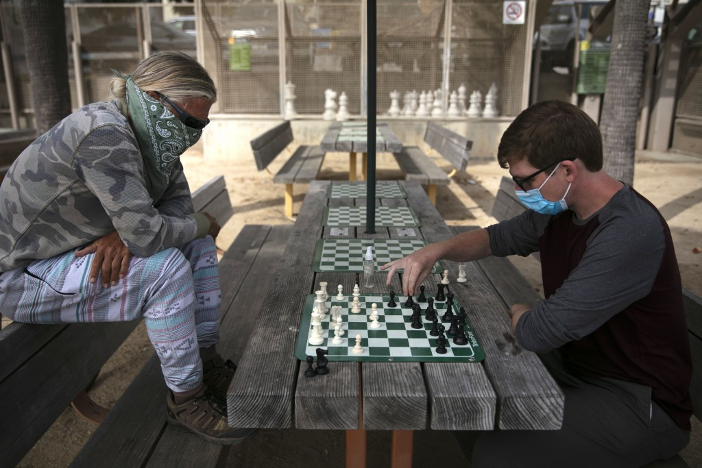 Wearing face coverings, John Williams, right, and Jeff Lee play chess Tuesday, June 23, 2020, in Santa Monica, Calif. The state Department of Public H...