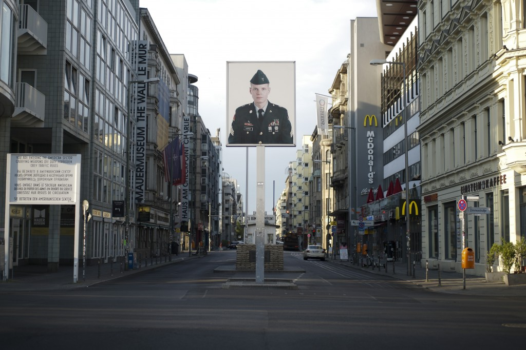 FILE - In this June 9, 2020, file photo, a picture of a former American soldier is displayed at the former U.S. army Checkpoint Charlie in Berlin, Ger...