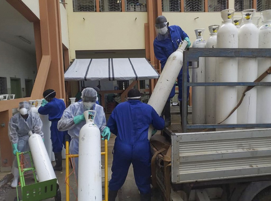 Medical workers offload cylinders of oxygen at the Donka public hospital where coronavirus patients are treated in Conakry, Guinea, on Wednesday, May ...