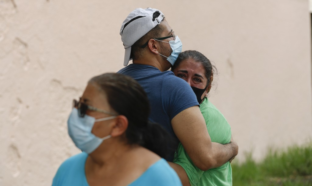 People embrace on he street as they wait for the all-clear to return to their apartment after an earthquake in Mexico City, Tuesday, June 23, 2020. Th...
