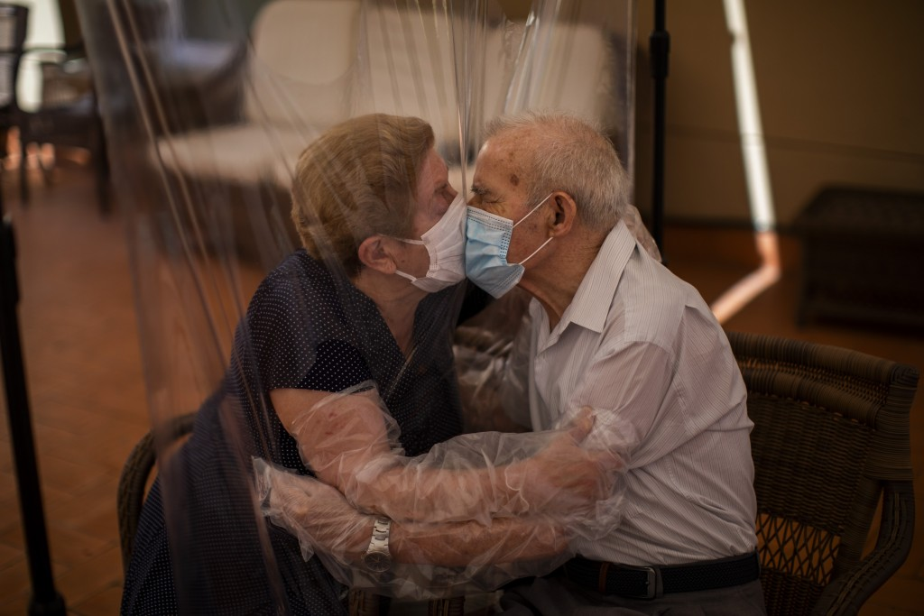 In this Monday, June 22, 2020 photo, Agustina Cañamero, 81, and Pascual Pérez, 84, hug and kiss through a plastic film screen to avoid contracting the...