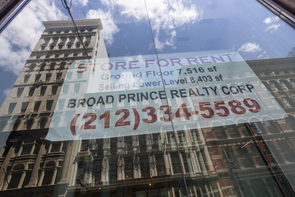In this May 7, 2020 photo, a store for rent sign hangs in the window of an empty storefront  in the Soho neighborhood of Manhattan in New York.  Many ...