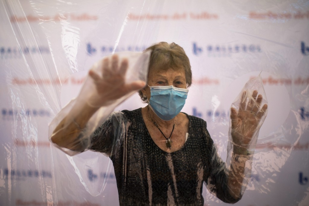 In this Monday, June 22, 2020 photo, Isabel Pérez López, 96, reacts behind a plastic film screen during the visit of her daughter, Beatriz Segura, 67 ...