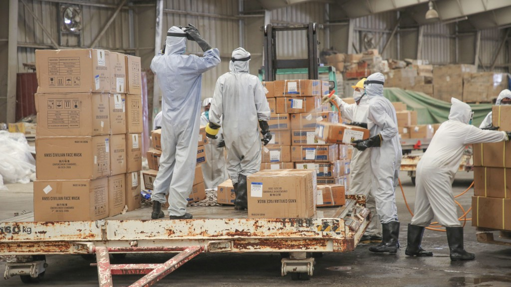 In this Wednesday, June 17, 2020, workers disinfect boxes of medical supplies on arrival at Sanaa International Airport in Sanaa, Yemen. The shipment ...