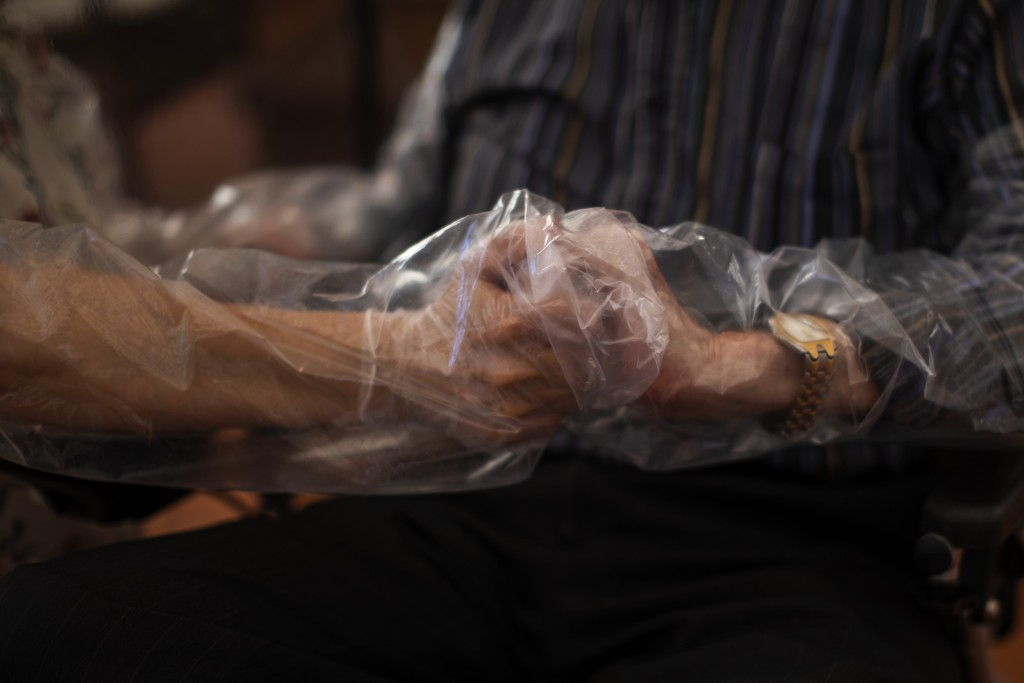 In this Monday, June 22, 2020 photo, Dolores Reyes Fernández, 61, holds the hands of her father José Reyes Lozano, 87, for the first time in nearly fo...