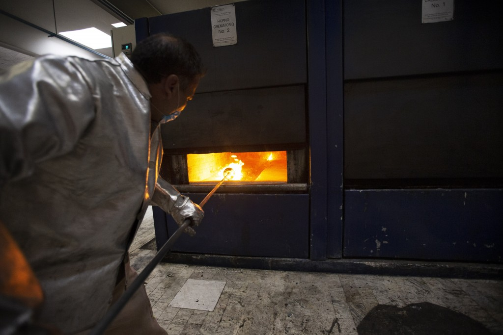 Worker Carlos Acuña Rios starts to collect the ashes of a COVID-19 victim from an oven after the remains where cremated at the Azcapotzalco crematoriu...