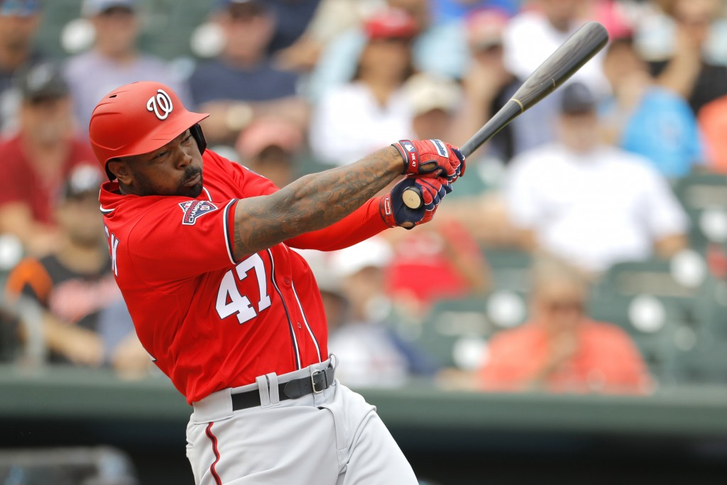 FILE - In this March 10, 2020, file photo, Washington Nationals designated hitter Howie Kendrick swings at a pitch from Miami Marlins' Caleb Smith dur...