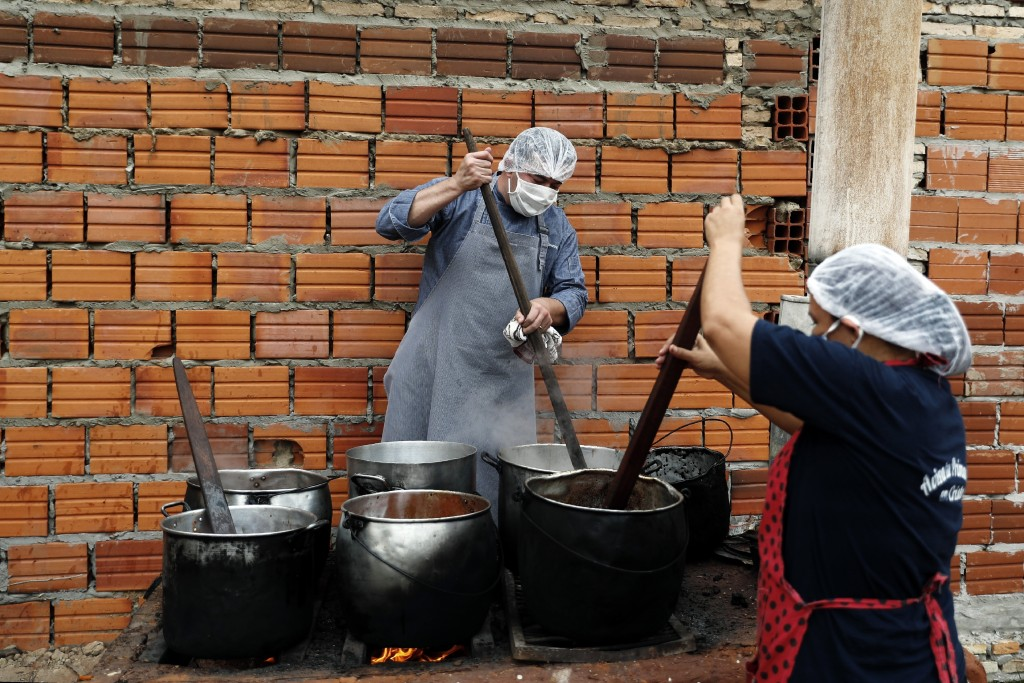 Walter Ferreira, left, and Laura Dure cook stew at a soup kitchen that feeds about 300 people daily in Luque, Paraguay, Monday, May 11, 2020. The U.N....