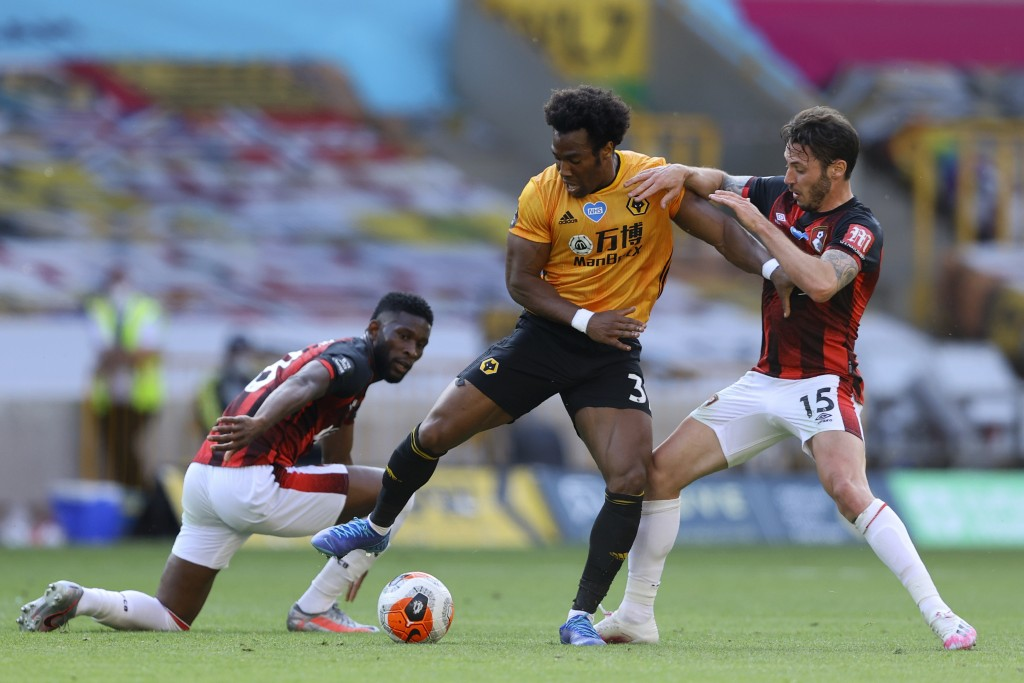 Bournemouth's Adam Smith, right, fights for the ball with Wolverhampton Wanderers' Adama Traore during the English Premier League soccer match between...