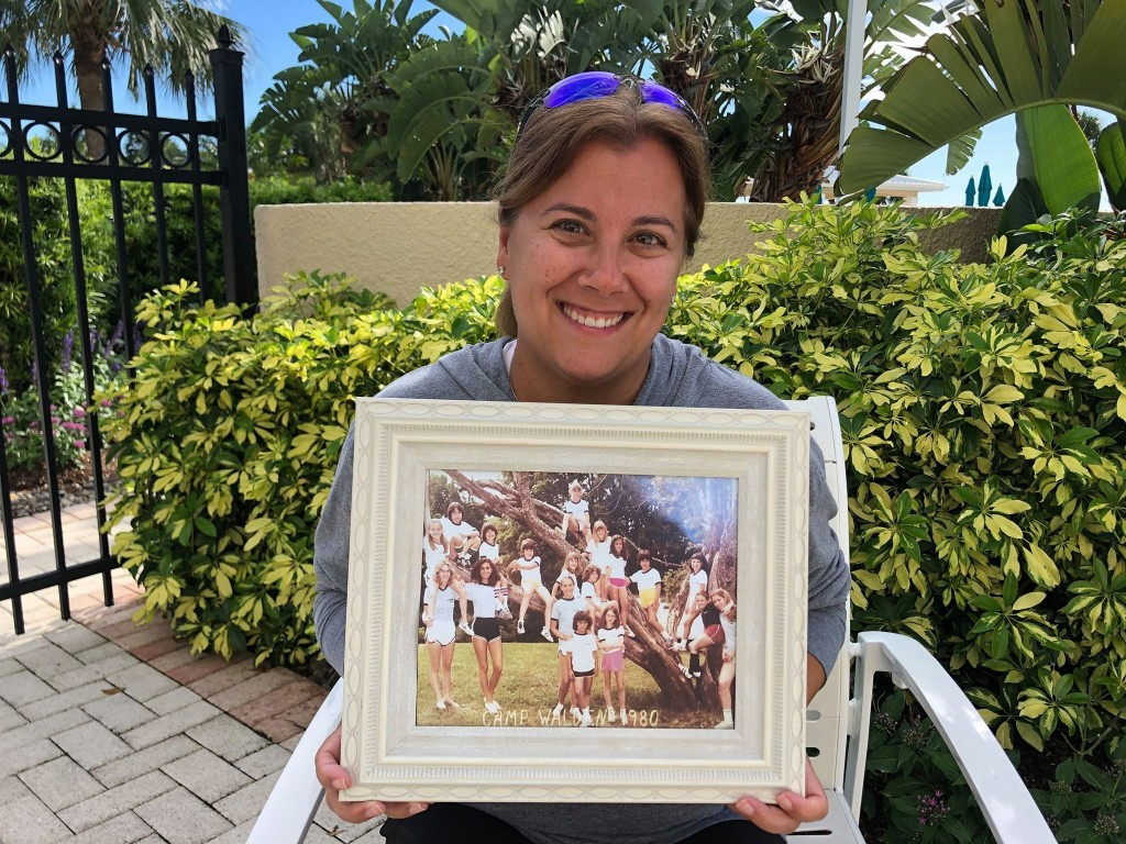 In this June 22, 2020, photo provided by Shaye Spector, Camp Walden Director Robyn Spector holds a group photo from one of her first summers at camp. ...